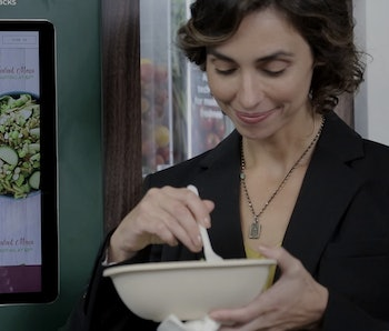 A woman is seen standing in front of a Sally robot by Chowbotics as she eats salad out of a bowl.
