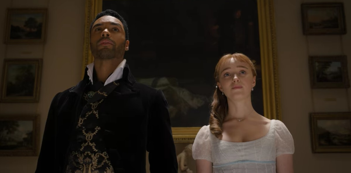 Simon and Daphne look at a painting together in 'Bridgerton.'