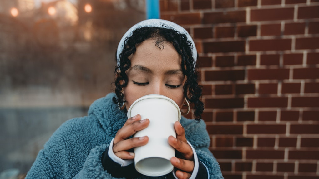 Young woman drinking hot chocolate bomb ahead of Valentine's Day