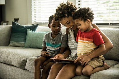 mother using tablet with young sons on couch