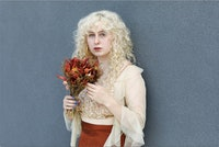 A portrait of Juliet Quick holding a bouquet of red flowers. She's standing against a gray wall.