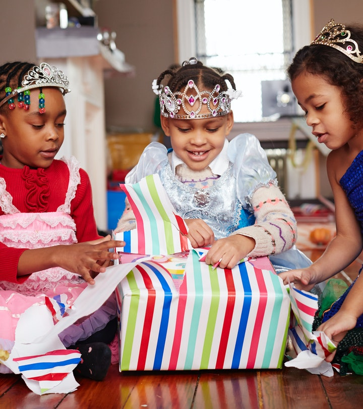 three girls wearing tiaras and opening presents