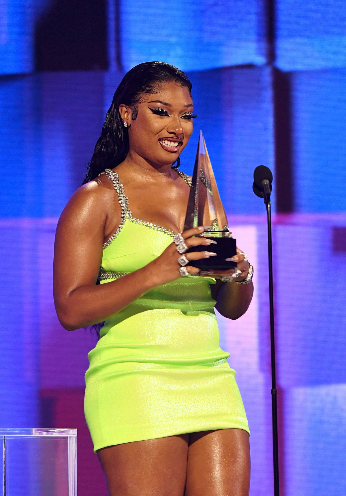 Megan in a bright green dress accepting an award