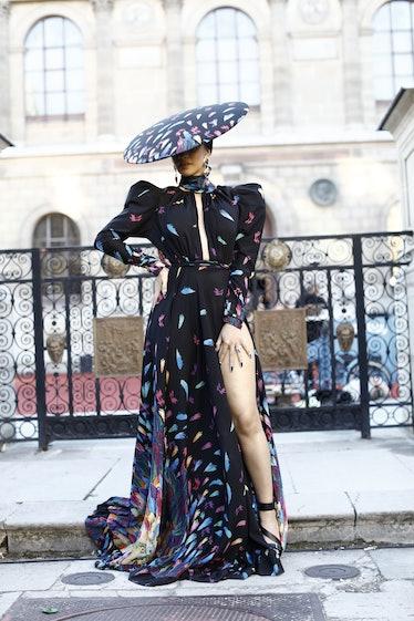 Cardi B in black dress with big disc-shaped hat.