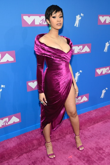 Cardi B in short hair and purple dress .