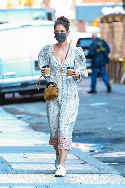 Katie Holmes steps out for coffee rocking a Bohemian chic dress for the occasion. The street style icon kept a black mask on and matched a pair of all-white canvas sneakers with the dress.