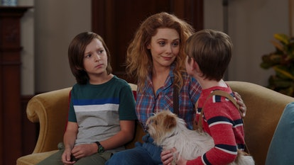 Wanda sits on the couch with her twin boys, who are 10 years old, with their new dog