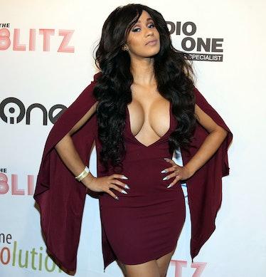 Cardi B in burgundy mini-dress with dramatic, wing-like sleeves.