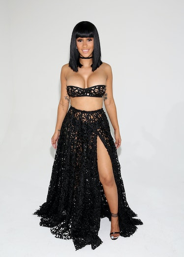 Cardi B in very small halter top and very long black skirt.