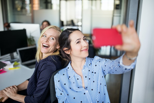 two women with side part taking a selfie in the office