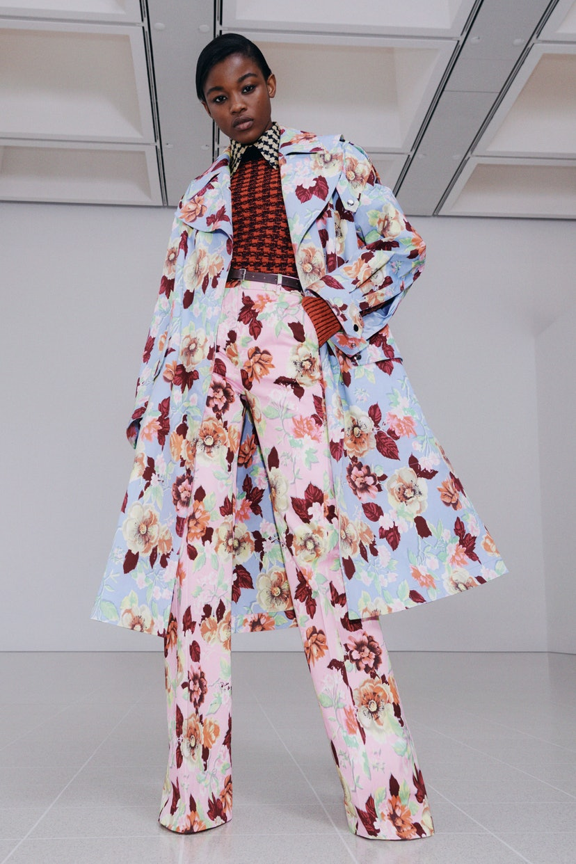 Model wearing floral coat and pants in Victoria Beckham's Fall/Winter 2021 collection