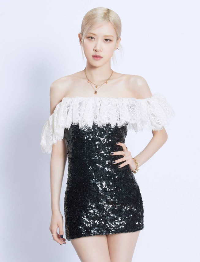 A portrait of BLACKPINK member Rosé. She's wearing a short sequined black dress, with white lace off-the-shoulder sleeves. Her blonde hair is pulled back from her face.