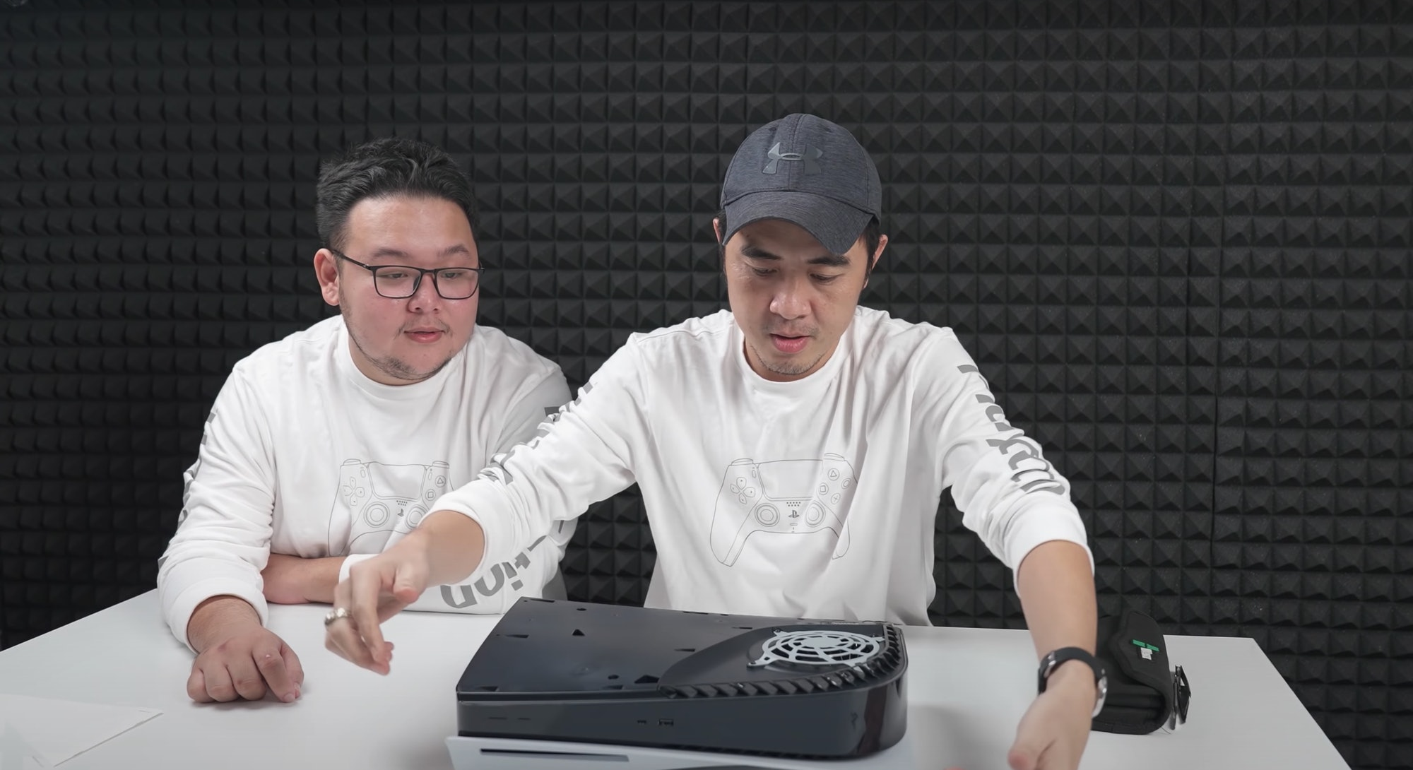 Two modders are seen disassembling a PS5.