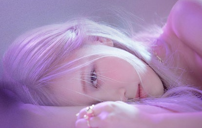 A portrait of Rosé. She is laying down with only half her face exposed, her pink hair dominates the frame.