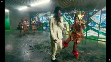 Burna Boy performs in a white suit.