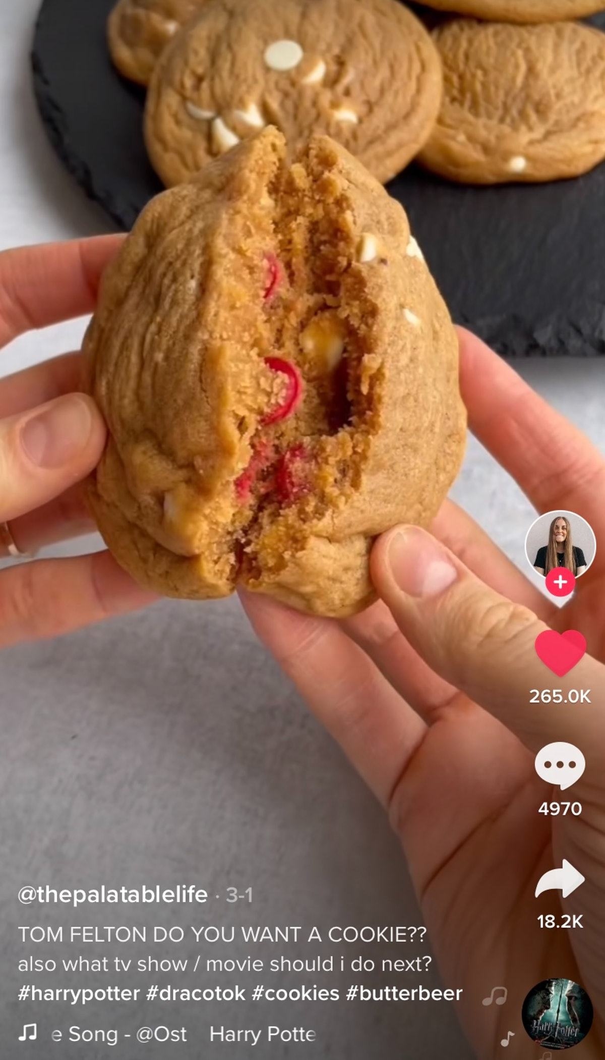 A woman breaks apart a butter beer 'Harry Potter' cookie with red M&M's inside.