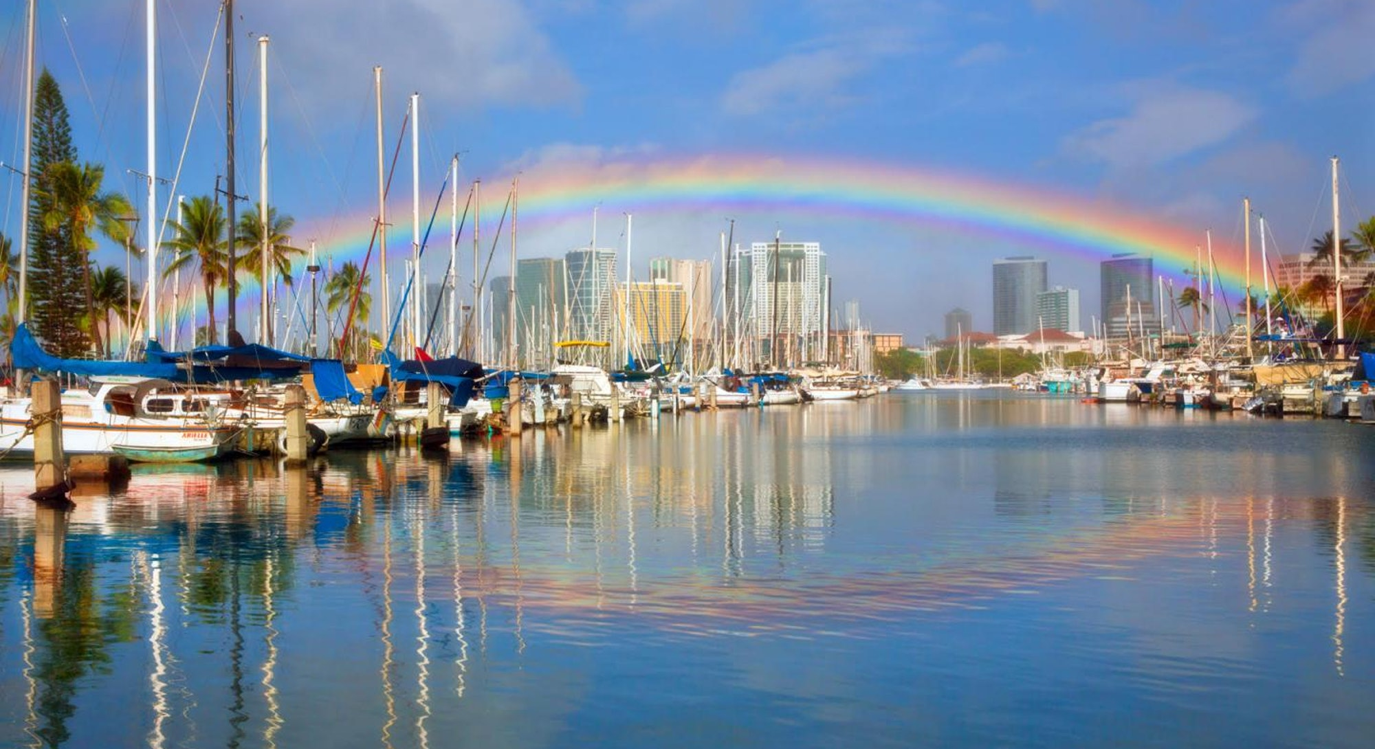 Rainbow over Honolulu Harbor with what appears to be its reflection. However, the reflected bow is not what it appears to be.