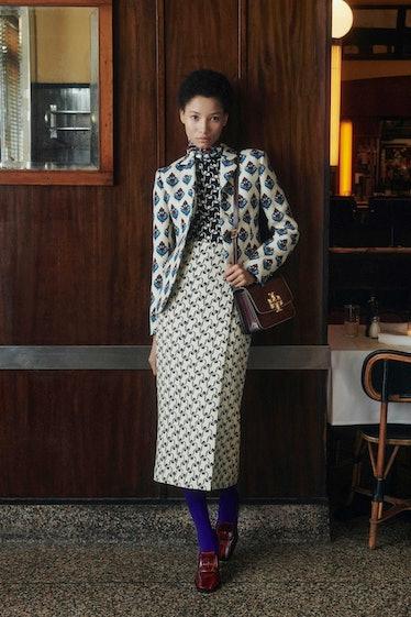 Model in mixed print skirt, blazer, and shirt