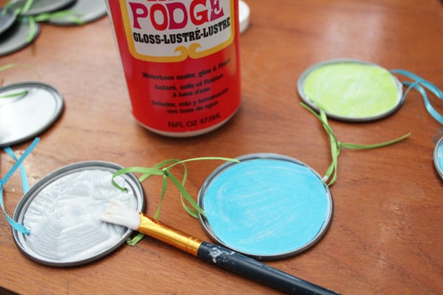 Use juice can lids to paint and make a garland.