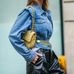 Natalia Verza aka Mascarada wears a white t-shirt, a blue denim jacket from Frankie Shop, a golden chain belt from Chanel, black leather crocodile pattern shiny shorts from Frankie Shop, a yellow tweed knitted quilted Chanel bag, on January 21, 2021 in Paris, France.