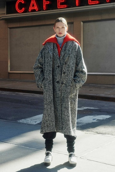 Model in overcoat with red sweater