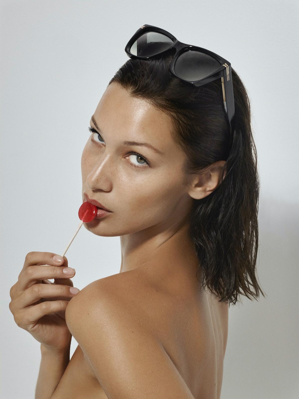 Bella Hadid holding a lollipop