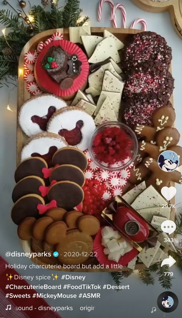 A Disney holiday-themed charcuterie board with cookies and peppermint sits on the kitchen counter.