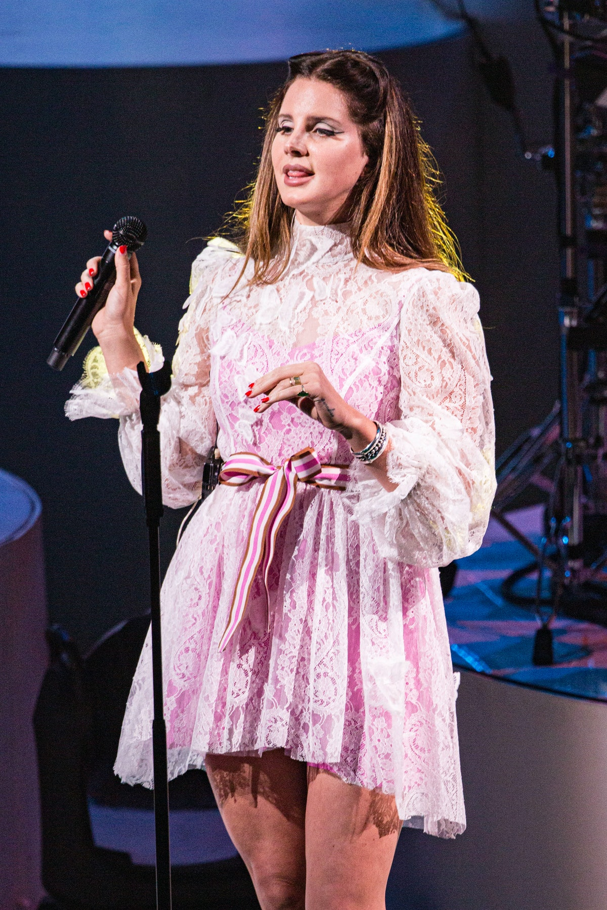 Lana Del Rey performing on stage in a pink babydoll dress
