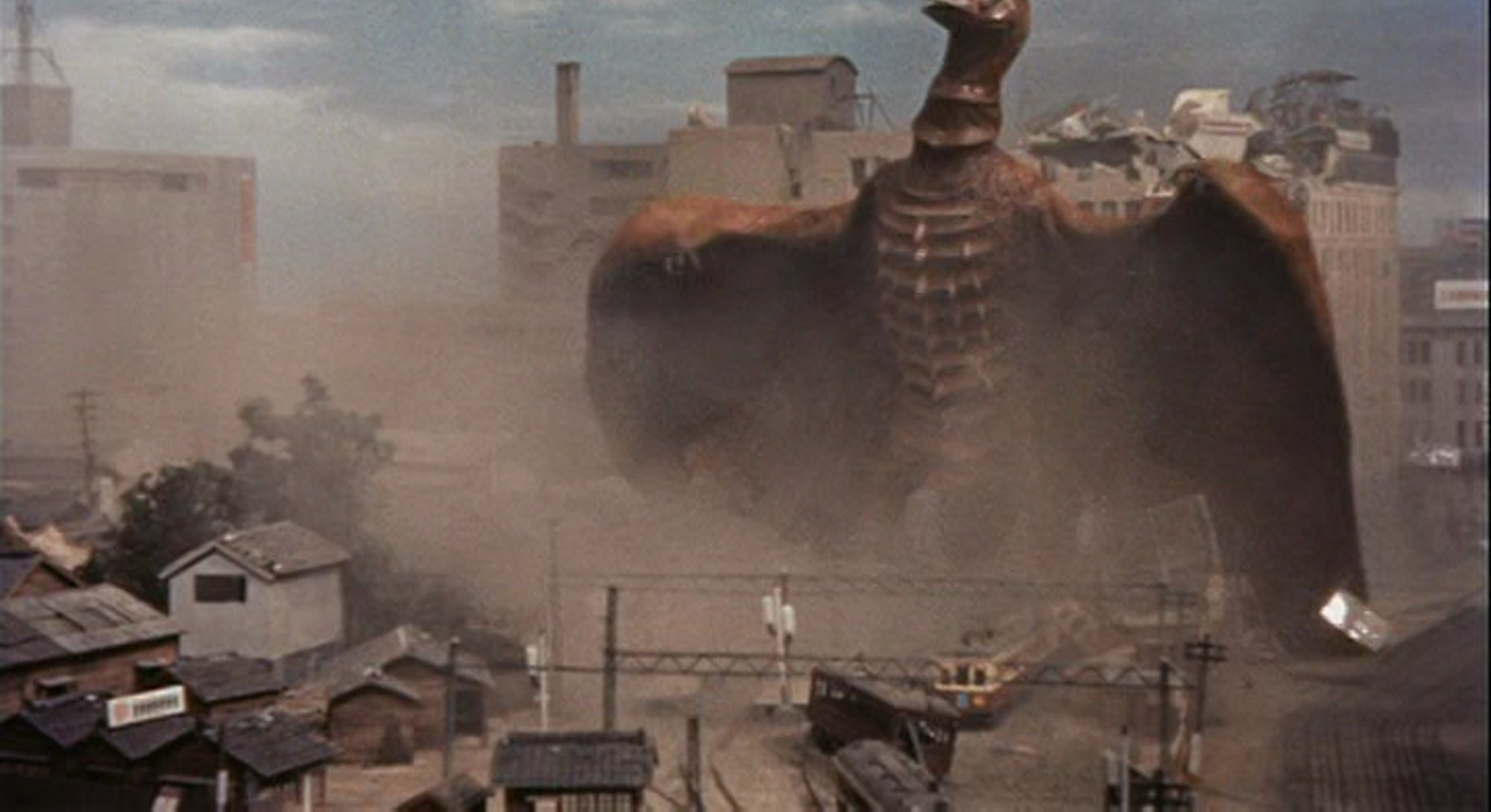 rodan monster destroying city with ruined building models in background