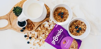 Two bowls of granola, an open package, and a jug of milk