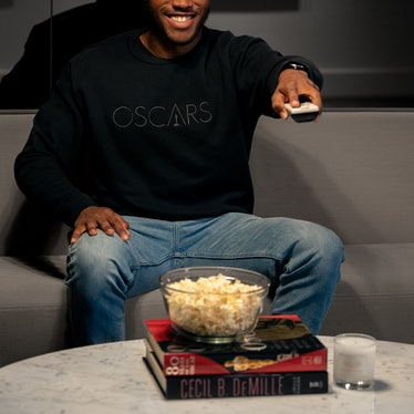 A person with popcorn using a remote