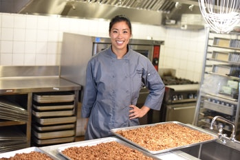 An image of a woman standing over a baking tray full of granola