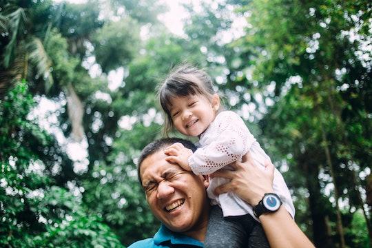 daughter sitting on dad's shoulders