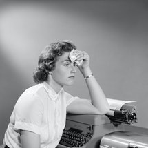 An anxious woman mops her forehead with a fever at her desk next to a typewriter. A mental health expert explains how anxiety can cause a fever.
