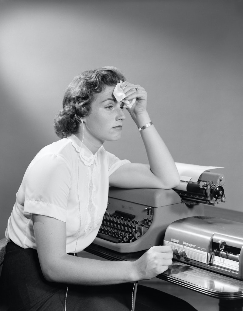 An anxious woman mops her forehead with a fever at her desk next to a typewriter. A mental health ex...