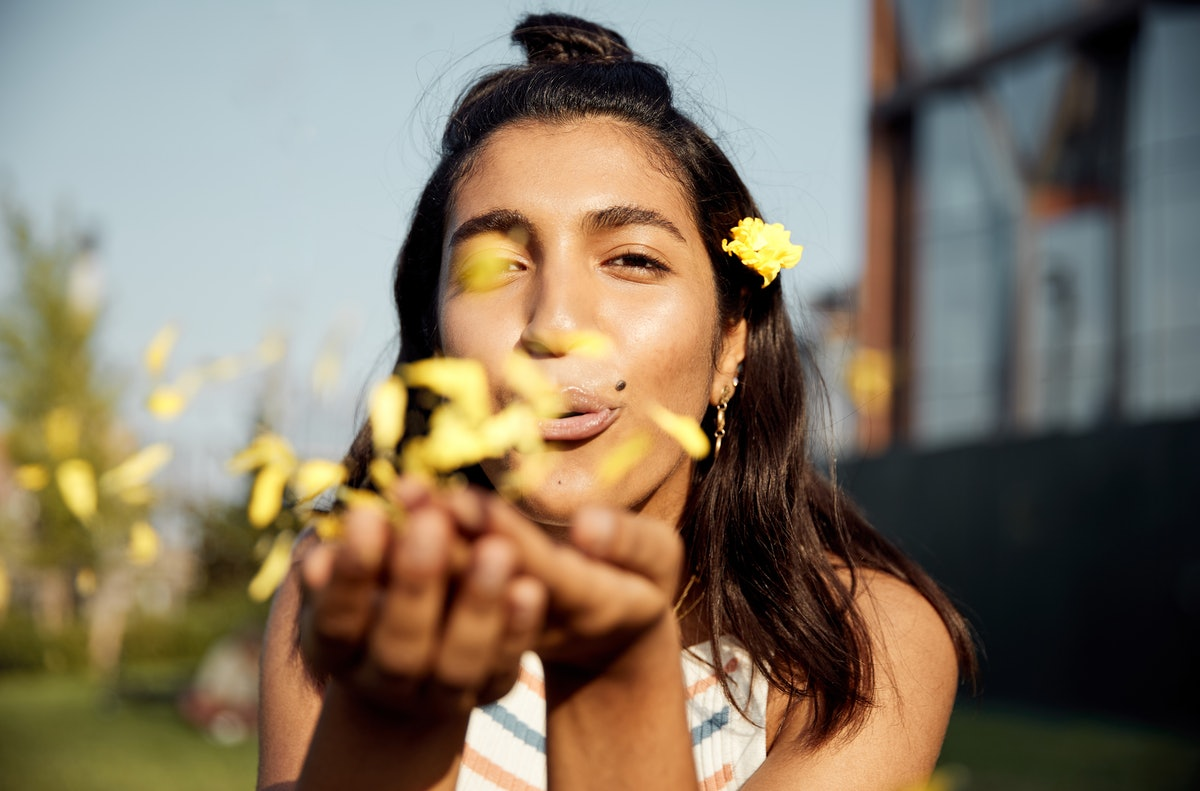 Young woman blowing flowers; flower captions for instagram, flower captions, flower caption