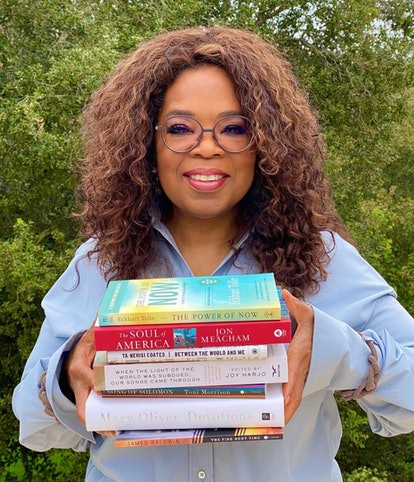 Oprah holding a stack of books.