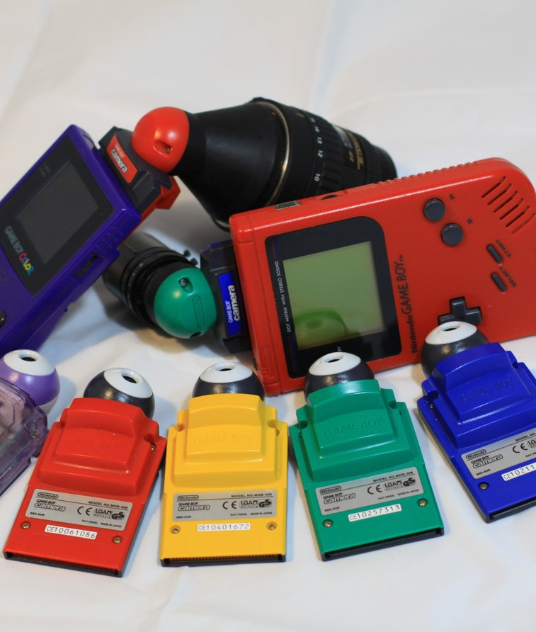 A family of different colored Game Boy Cameras with Game Boys and DIY camera lens attachments.