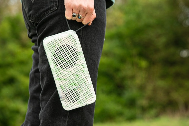 A view of a white and green Gomi speaker held next to a person's leg