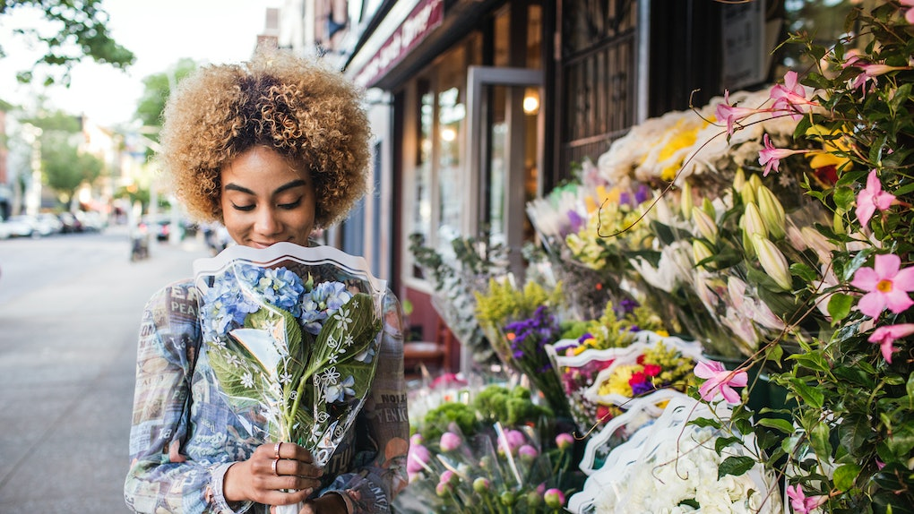 Young woman smelling flowers; flower captions for instagram, flower captions, flower caption