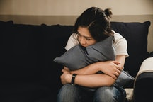 woman sitting on couch, hugging pillow