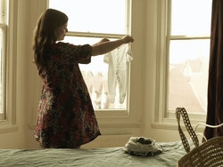 smiling pregnant woman standing by window, holding up a newborn onesie