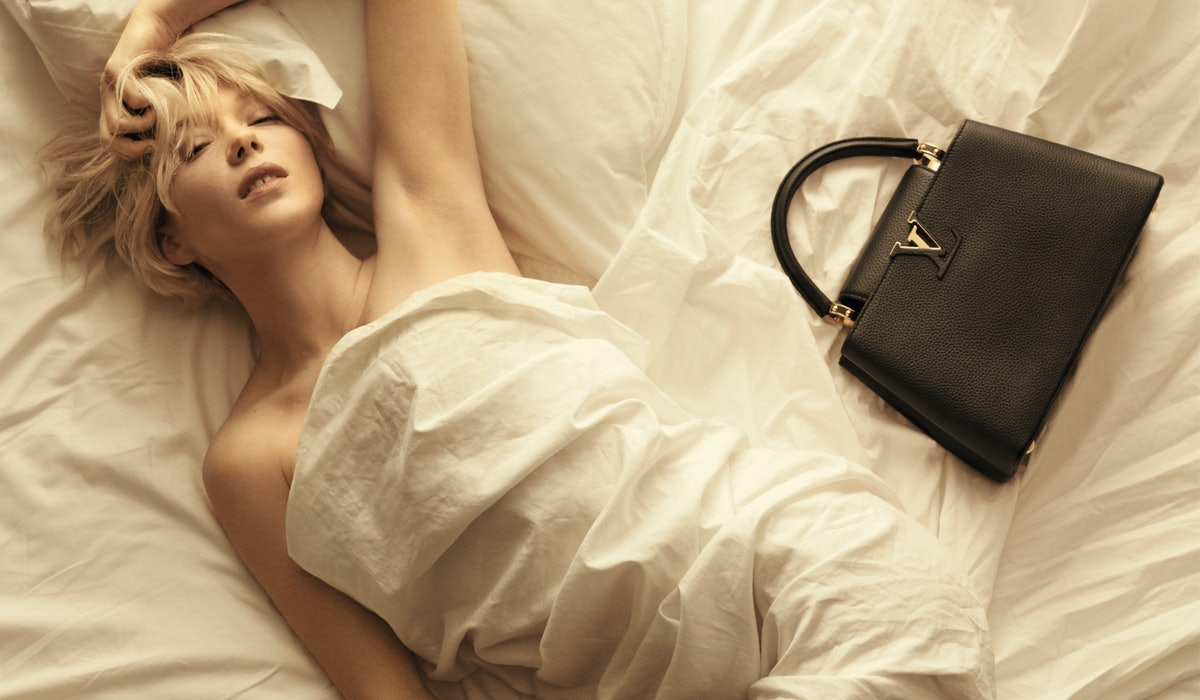 Léa Seydoux lying in bed with a Louis Vuitton bag