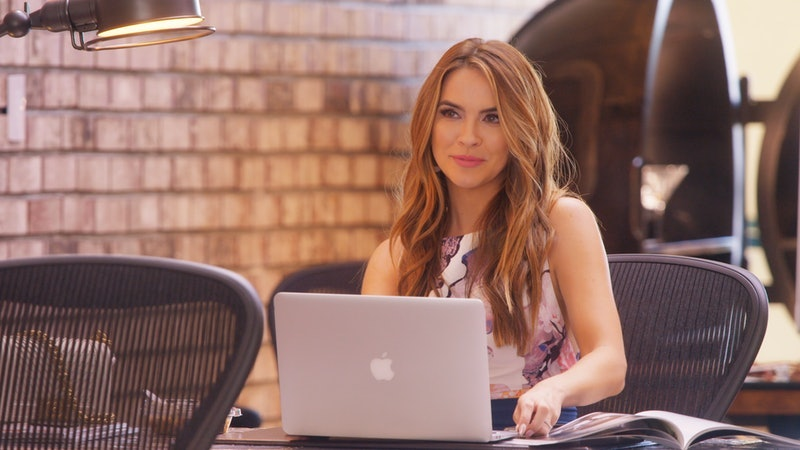 Chrishell Stause sits behind her laptop at her desk in the Oppenheim Group office
