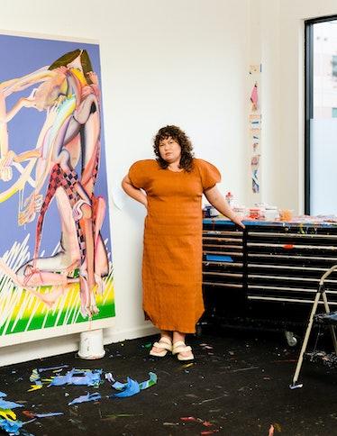 "Christina Quarles in her studio in front of ""New Moon,"" 2021. Quarles wears a Mara Hoffman dress; Ji..."