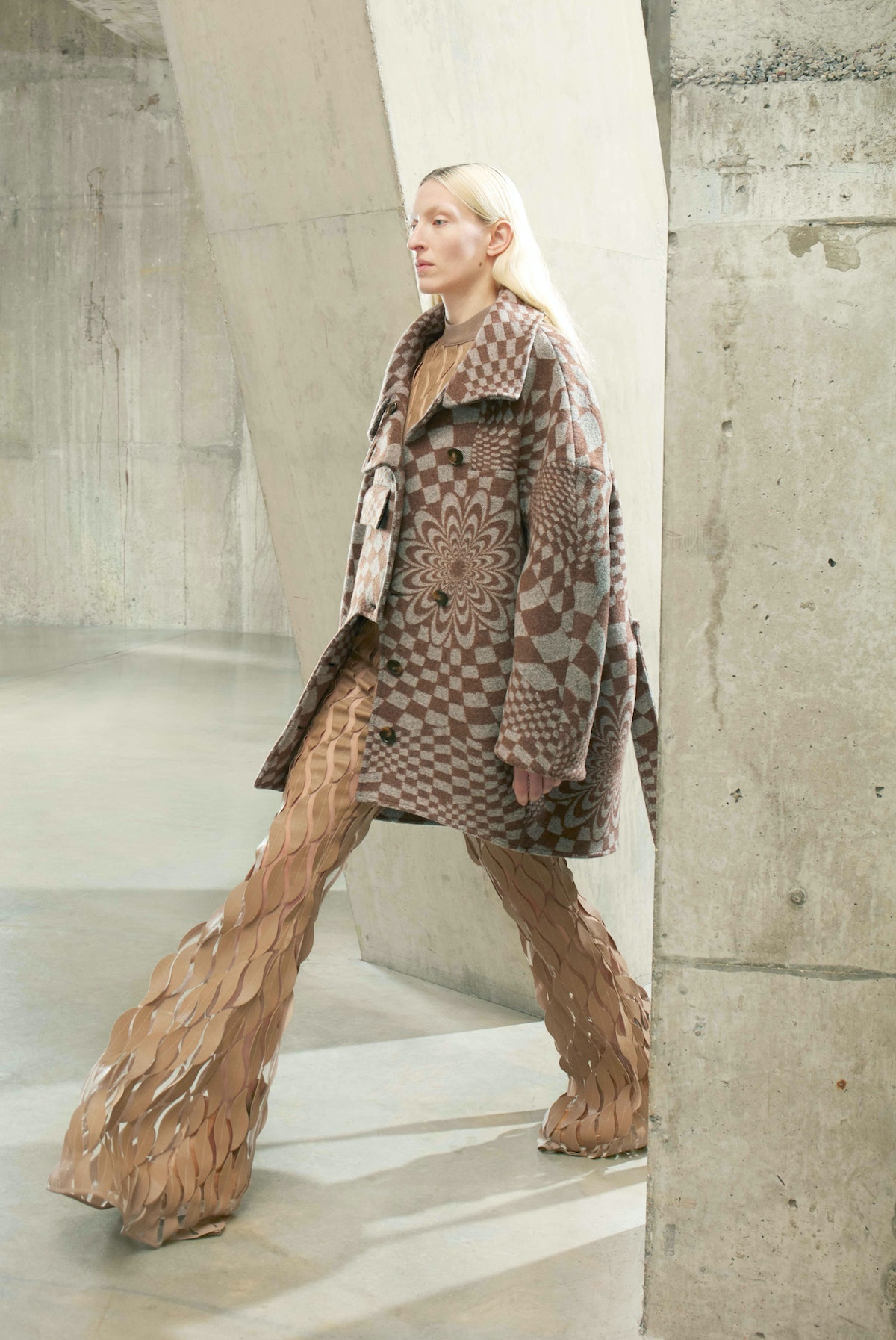 Model in tan checkered coat with flare pants