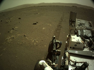 Perseverance rover seen in foreground on the surface of Mars, with tire marks trailing behind it