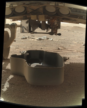 A picture of the Ingenuity helicopter tucked inside the Perseverance rover on the surface of Mars.
