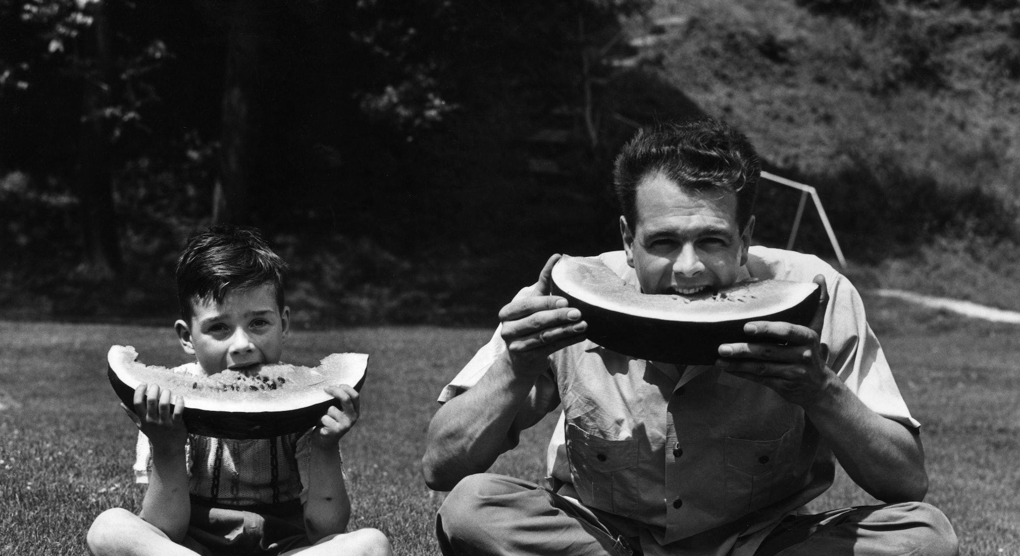 man and boy eat watermelon