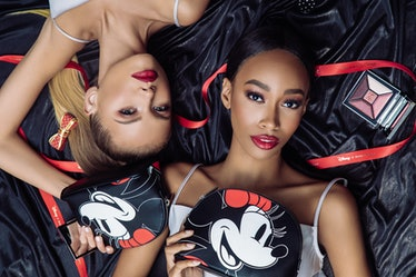 Two women lay on the floor surrounded by the House of Sillage Mickey and Minnie Mouse Disney makeup ...